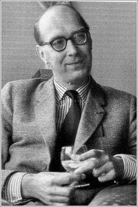 the poet Philip Larkin holds a drink and smiles.